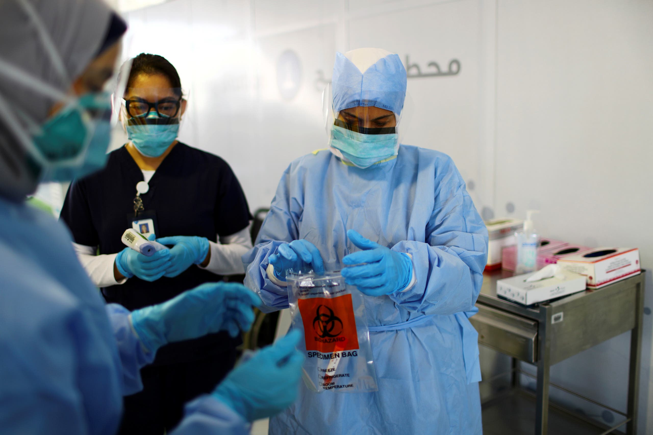 A member of medical staff wearing a protective face mask and gloves carries a swab tested during drive-thru coronavirus disease testing (COVID-19) at a screening centre in Abu Dhabi, United Arab Emirates March 30, 2020. (Reuters)