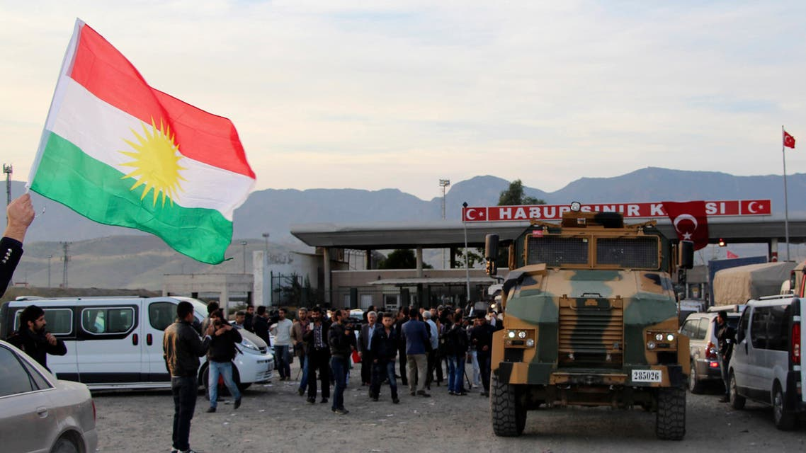 A man waves a Kurdistan flag as a Turkish military truck escorts a convoy of peshmerga vehicles at Habur border gate, which separates Turkey from Iraq, near the town of Silopi in southeastern Turkey, October 29, 2014. (Reuters)