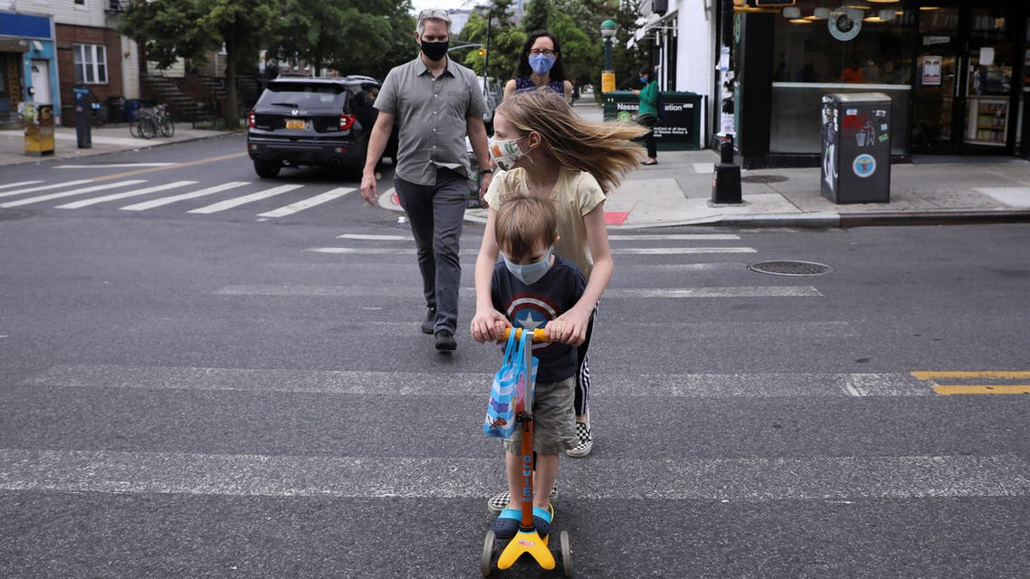 Lydia Hassebroek scoots to pick up the end of year school materials with her parents and brother Felix before digital graduation during the outbreak of the coronavirus disease (COVID-19) in Brooklyn, New York, U.S., June 11, 2020. REUTERS/Caitlin Ochs