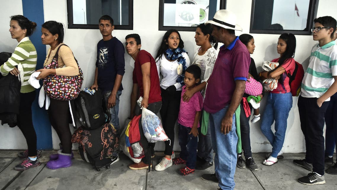 Members of the Mendoza Landinez family wait in line to apply for the status of refugee, outside the Peruvian immigration offices, in Tumbes, Peru, on August 25, 2018, to apply for the status of refugee, even though they are out of the time limit imposed by authorities to allow the passage of Venezuelans without a passport. On foot, by bus, on the backs of juddering trucks, like tens of thousands of others they slogged for days along the Pan-American highway through Colombia and Ecuador. Grubby and sleepless, their goal was to reach Peru, a sanctuary of sorts for a desperate Venezuelan family. Exhausted and swept by the endless wash of traffic noise on the highway's shoulder, the Mendoza Landinez family had the additional pressure of a deadline: to enter Peru before new rules required them to produce a passport.