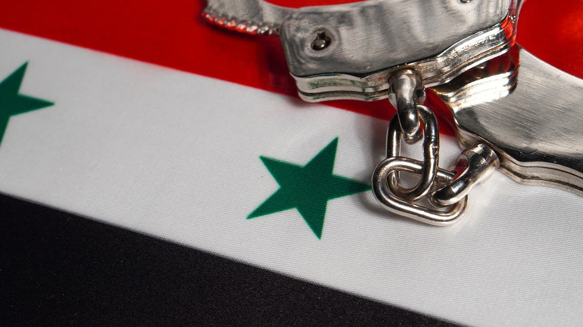 Handcuffs with hand on Syria flag stock photo