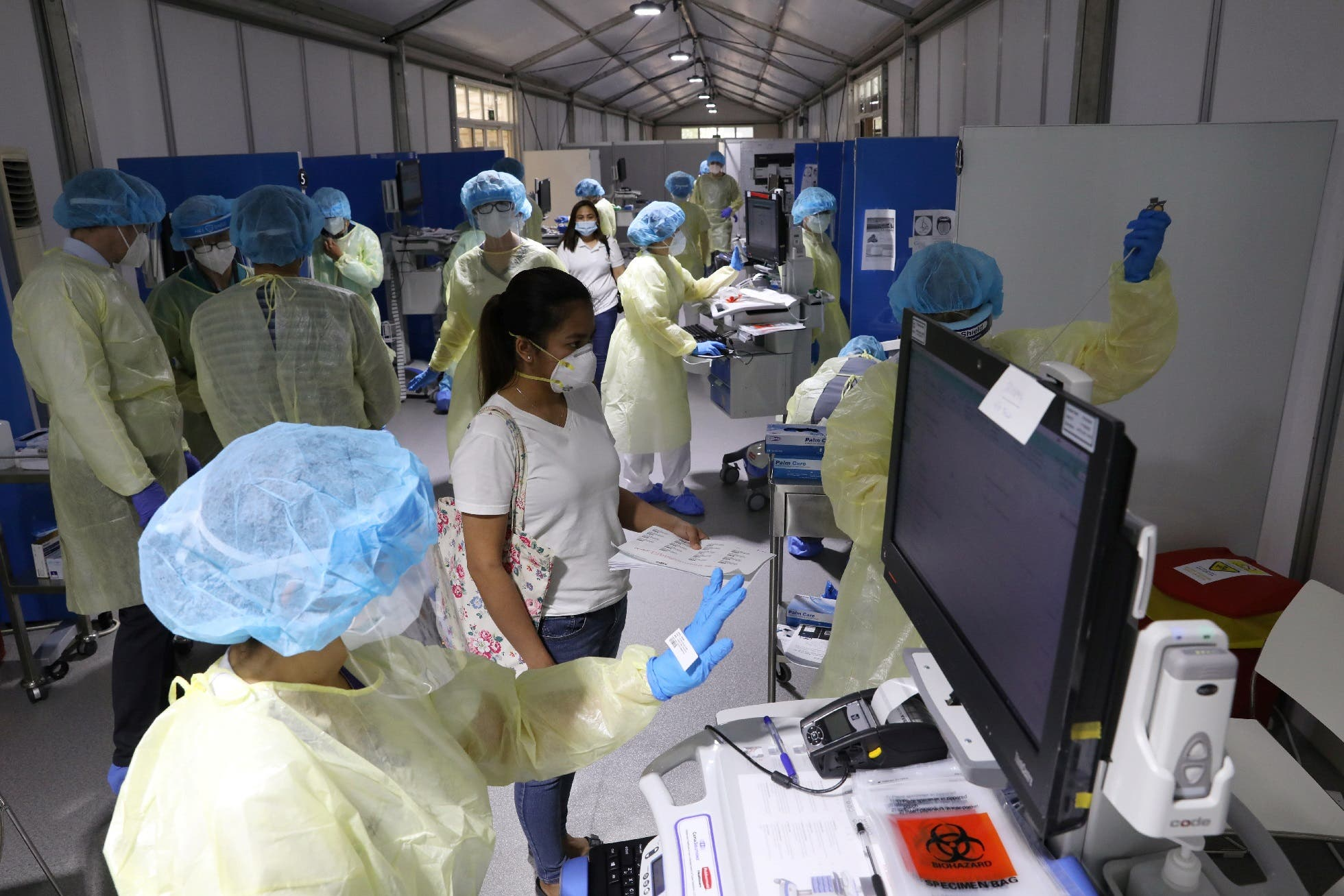 A woman waits to be tested by medical staff wearing protective equipment, amid the coronavirus outbreak, at a hospital in Abu Dhabi, UAE, April 20, 2020. (Reuters)