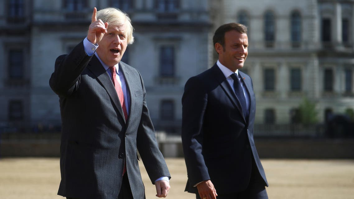 British Prime Minister Boris Johnson gestures as he and French President Emmanuel Macron walk, after watching The Red Arrows and La Patrouille de France perform a flypast, at Horse Guards Parade in London, Britain, June 18, 2020. REUTERS/Hannah McKay/Pool
