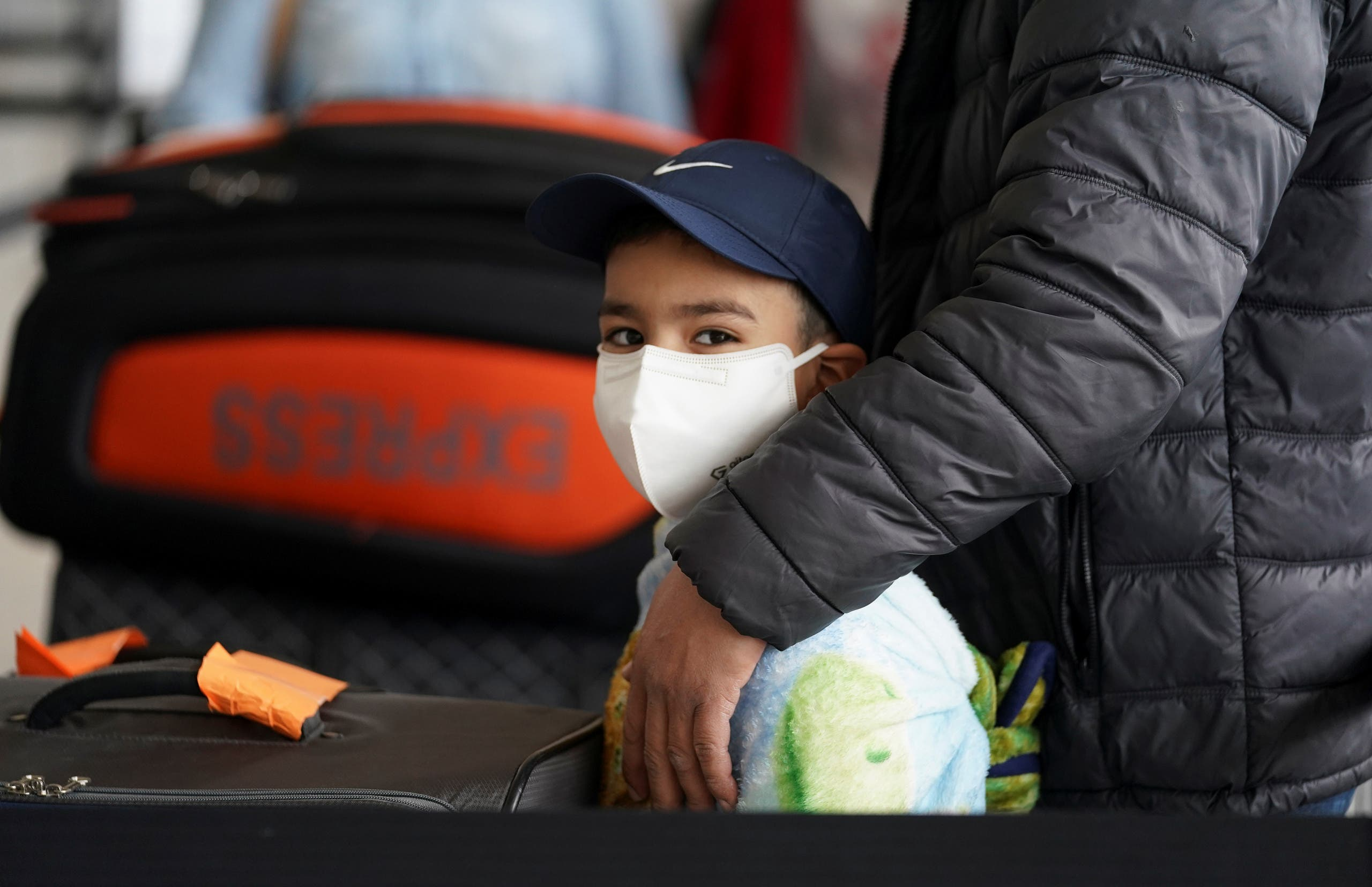 A boy wearing a face mask stands in the check-in line with his family at Dulles International Airport a day after U.S. President Donald Trump announced travel restrictions on flights from Europe to the United States for 30 days to try to contain coronavirus, in Dulles, Virginia, U.S., March 12, 2020. (Reuters)