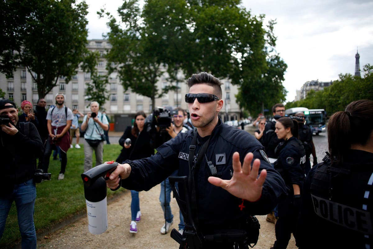 A police officer keeps people at a distance while anticolonial activist cover French military commander Joseph Gallieni statue with a black cloth, in Paris, Thursday, June 18, 2020. (AP)