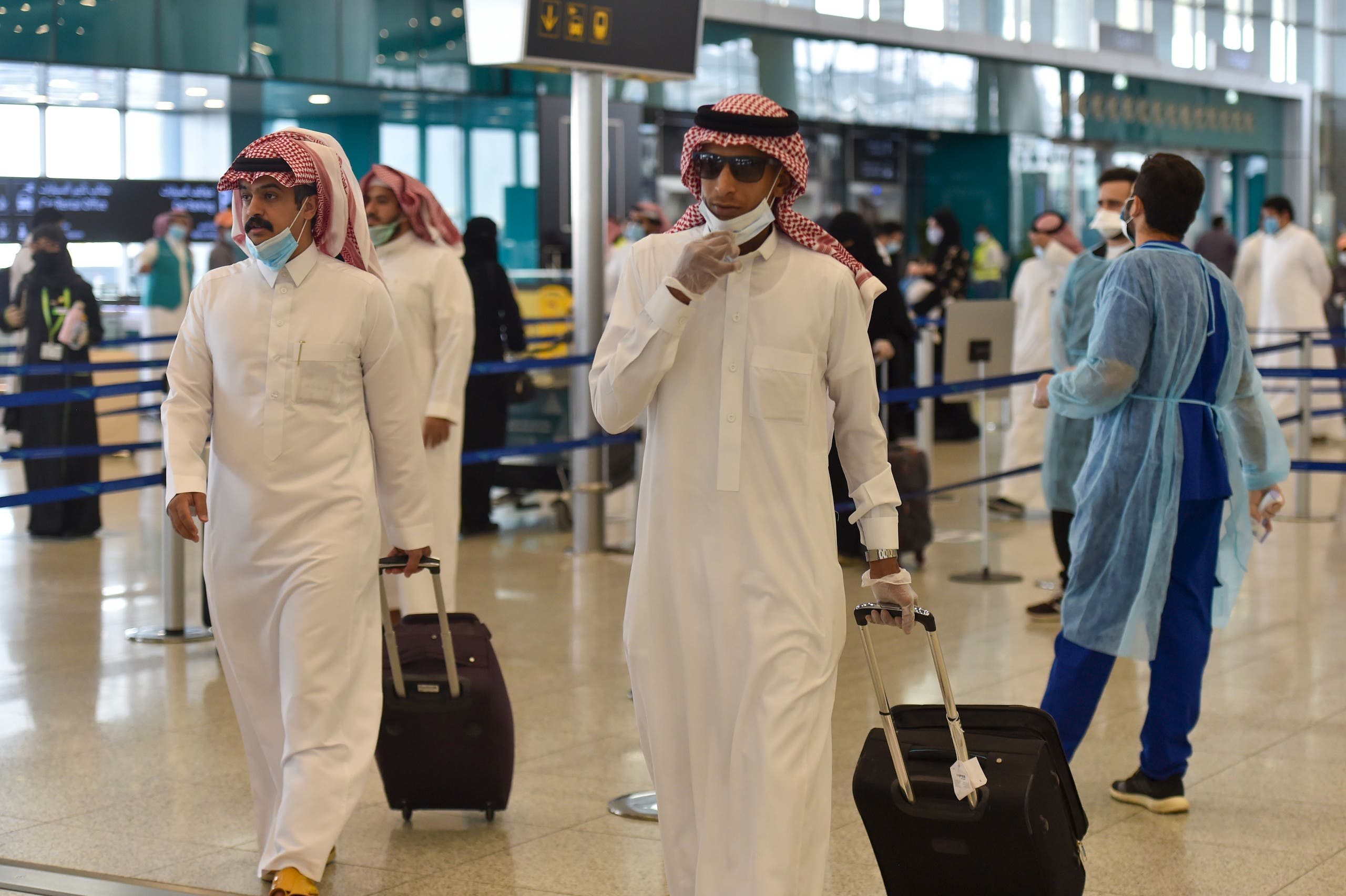 Saudi passengers queue for a temperature check at terminal 5 in the King Fahad International Airport, designated for domestic flights, in the capital Riyadh. (File photo: AFP)