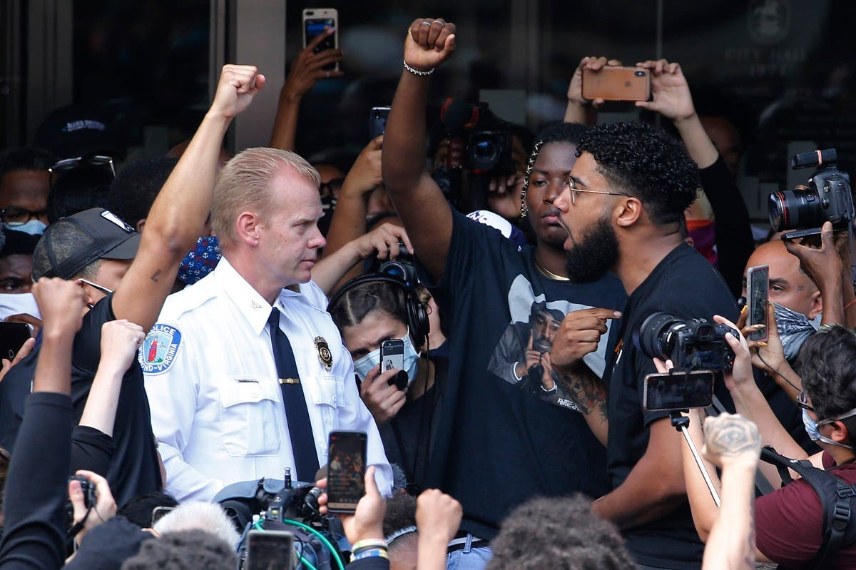Richmond Police Chief William Smith, left, is confronted by a protester as he attempts to address a large crowd in front of City Hall, Tuesday June 2, 2020, in Richmond, Va.