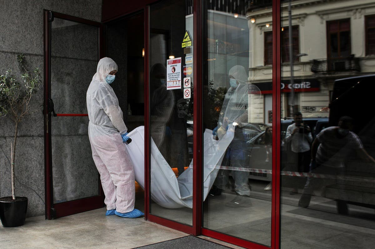 Forensic medicine staff carry a body bag, allegedly containing the remains of Gholamreza Mansouri, outside a hotel in downtown Bucharest. (Reuters)