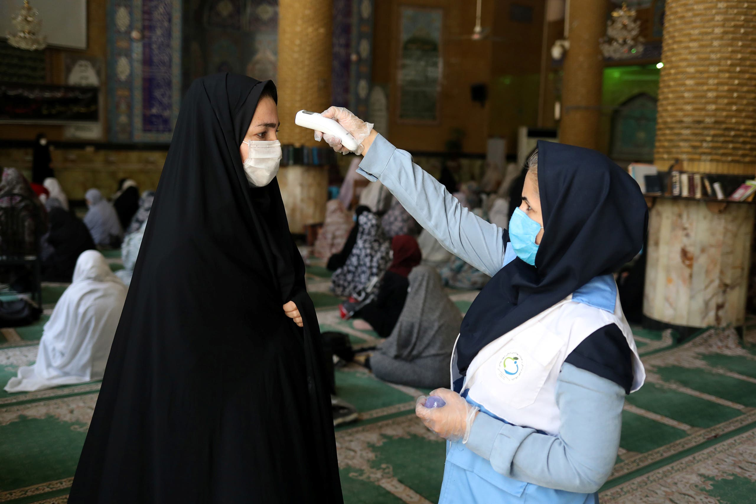 An Iranian woman wearing a protective face mask checks the temperature of a worshipper before attending the Friday prayers in Qarchak Jamee Mosque, following the outbreak of the coronavirus disease (COVID-19), in Tehran province, in Qarchak, Iran, June 12, 2020. (Reuters)