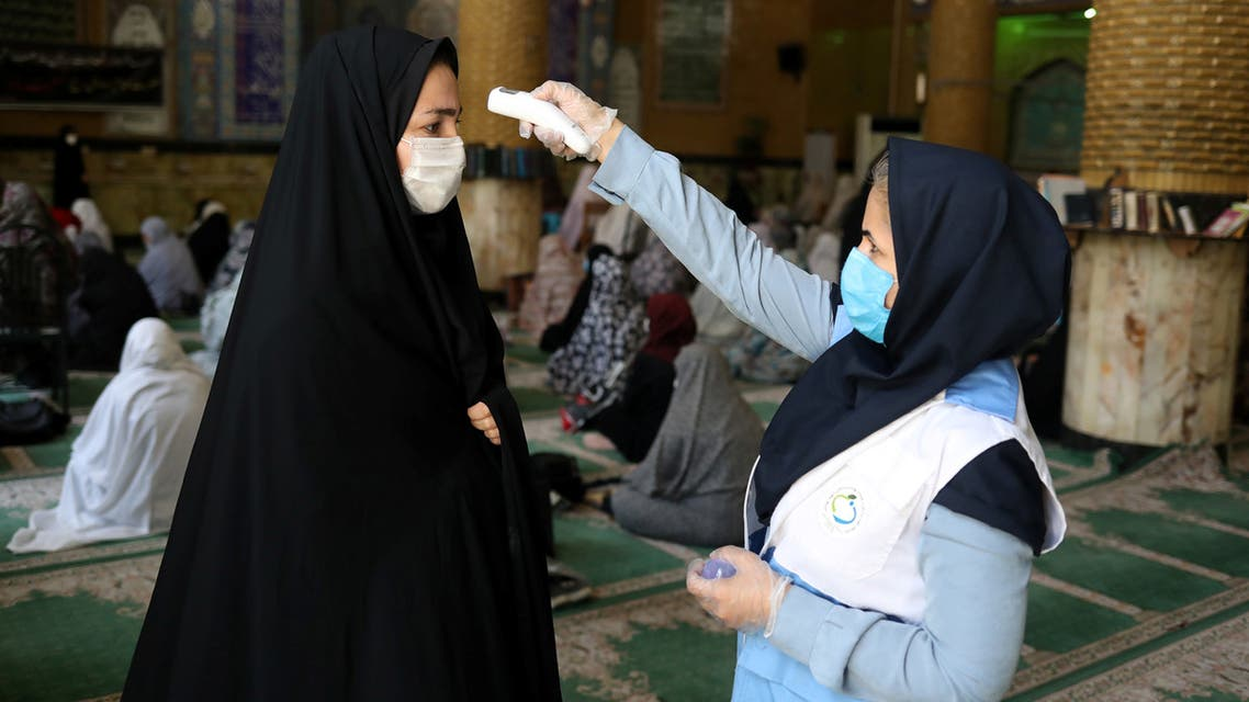 An Iranian woman wearing a protective face mask checks the temperature of a worshipper before attending the Friday prayers in Qarchak Jamee Mosque, following the outbreak of the coronavirus disease (COVID-19), in Tehran province, in Qarchak, Iran, June 12, 2020. WANA (West Asia News Agency)/Ali Khara via REUTERS ATTENTION EDITORS - THIS PICTURE WAS PROVIDED BY A THIRD PARTY