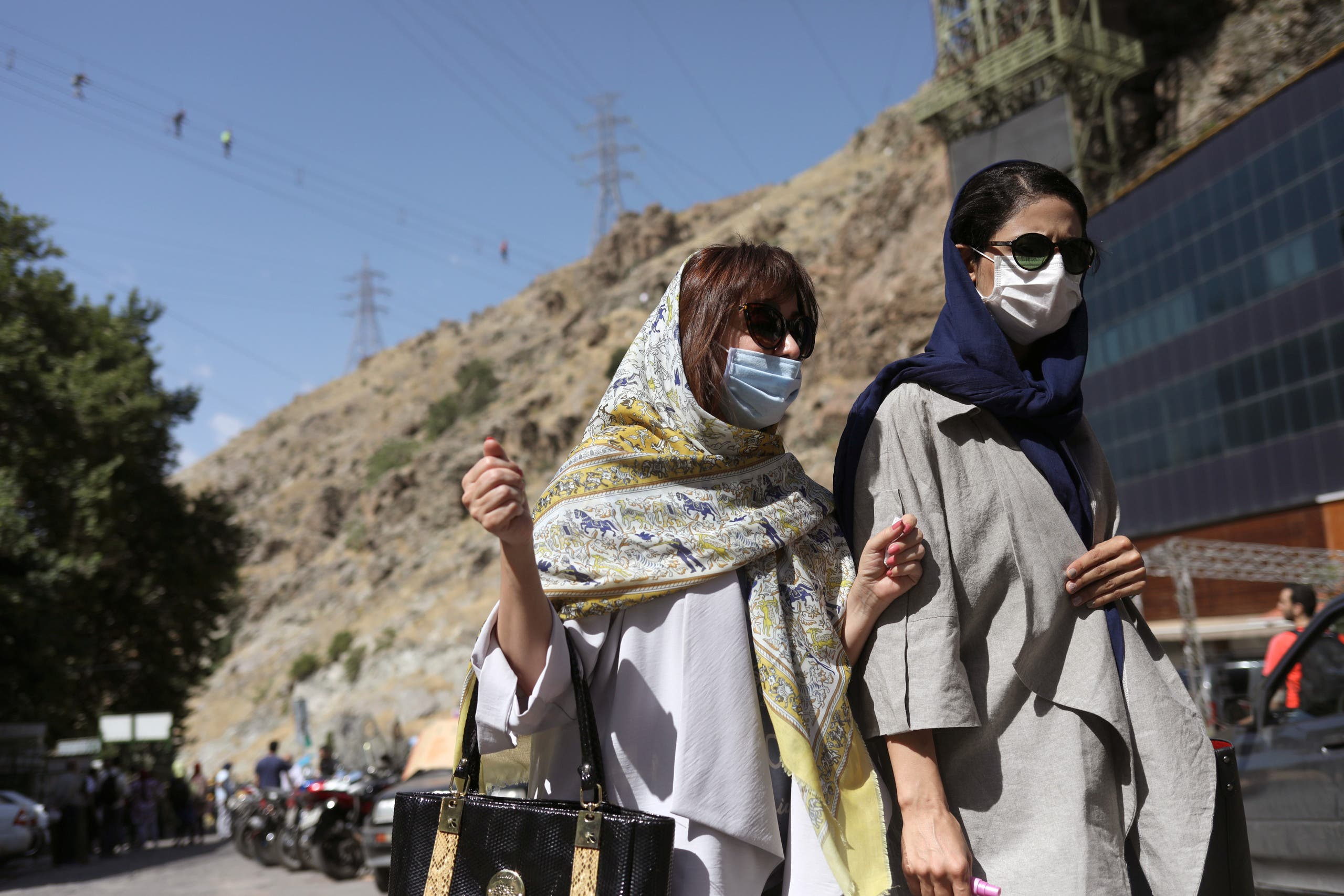 Iranian women wearing protective face masks walk in Darband street, following the outbreak of the coronavirus disease (COVID-19), in Tehran, Iran June 12, 2020. (Reuters)