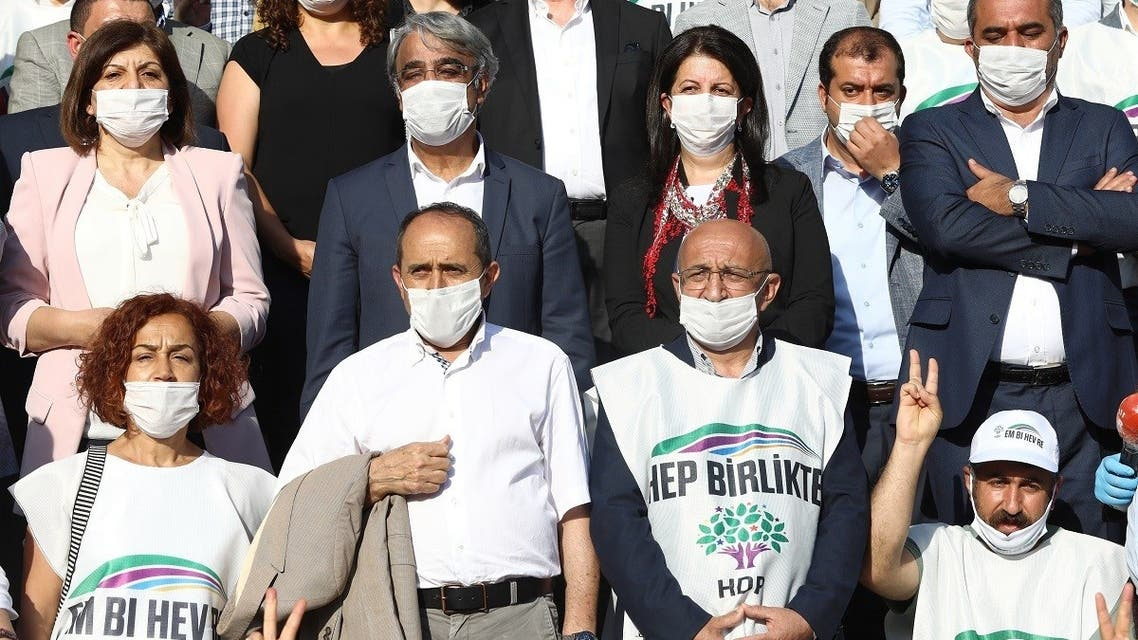 Co-chairs of the pro-Kurdish Peoples Democratic Party (HDP) Mithat Sancar (2nd L) and Pervin Buldan (3rd R) pose for a group photograph at Parliament Park following the march for democracy, which started in Edirne and Hakkari on June 15, and ended with a press release at Parliament Park in Ankara on June 20, 2020. (AFP)