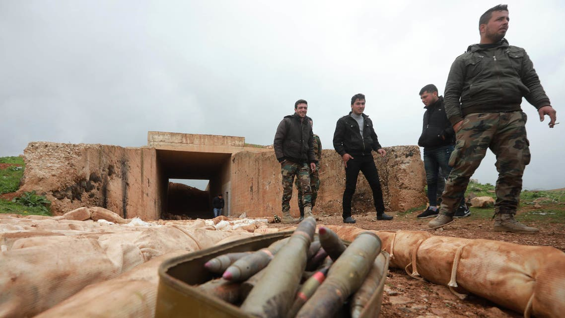 Syrian soldiers stand next to ammunition and packs they say are of C-4 explosives that were found in the southern province of Daraa on February 27, 2019, during a government-organised trip for journalist. Daraa was once seen as the cradle of Syria's seven-year uprising, but in July regime forces took back control through a military push and deals that saw rebels surrender.