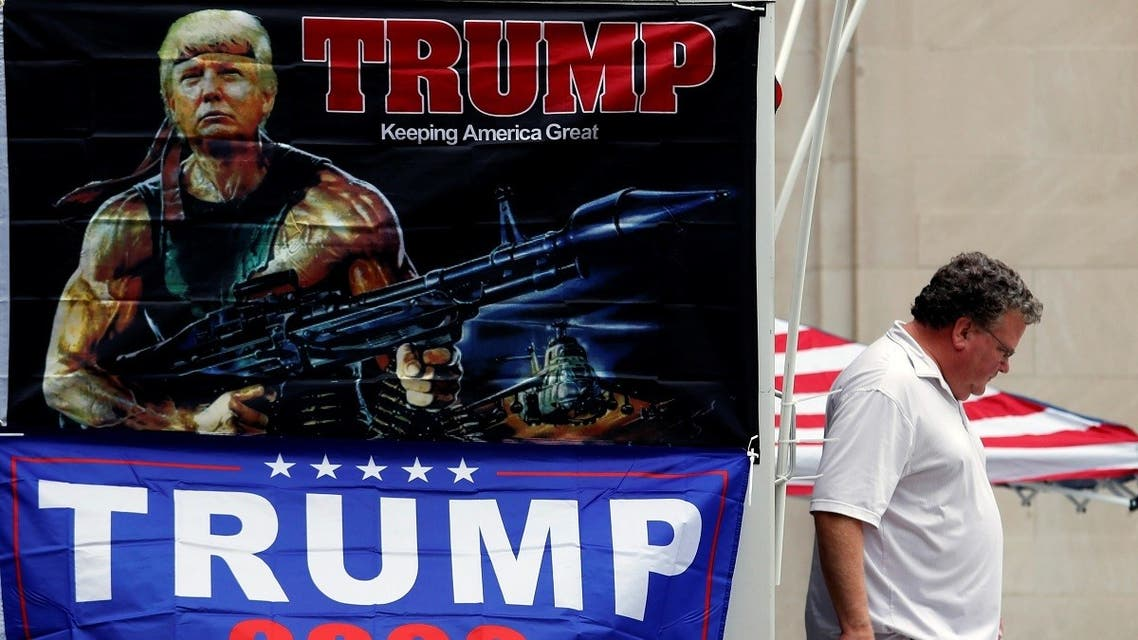 A man walks past banners of U.S. President Donald Trump sits on a roadblock near the BOK Center for his upcoming rally in Tulsa. (Reuters)