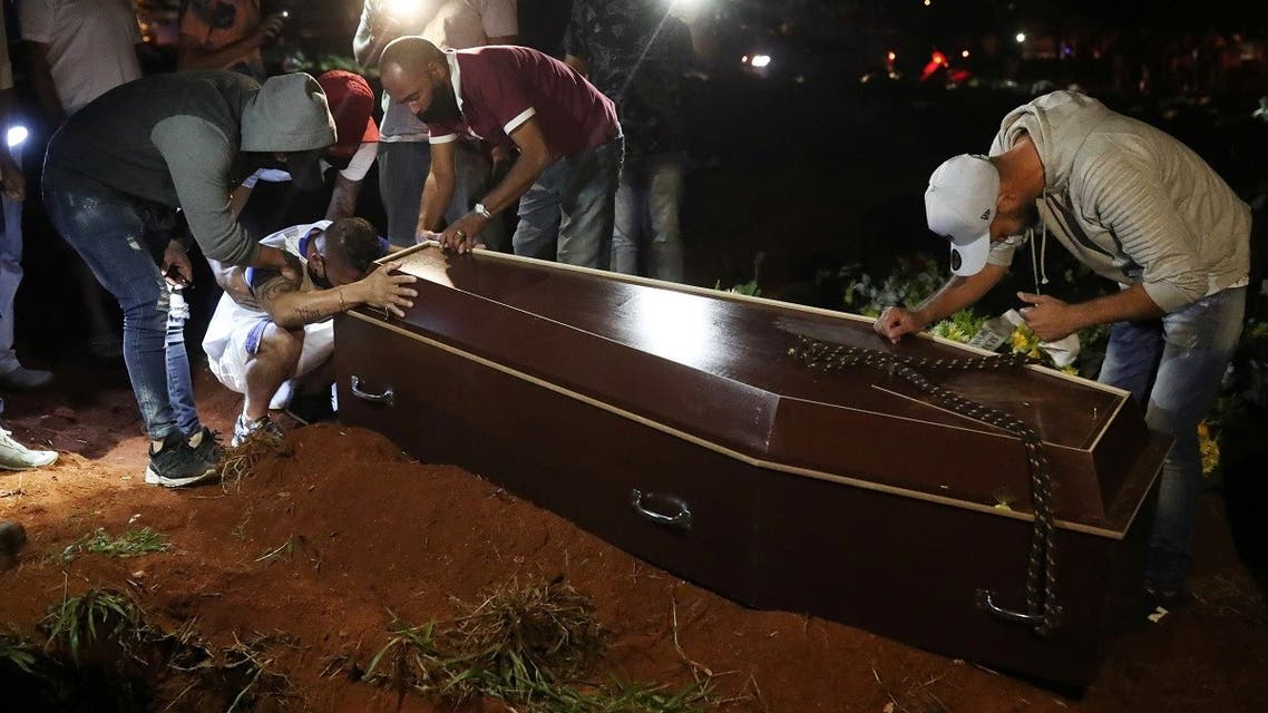A man reacts as the coffin of his father, who died from the coronavirus disease (COVID-19), is prepared to be buried at Vila Formosa cemetery, Brazil's biggest cemetery. (Reuters)