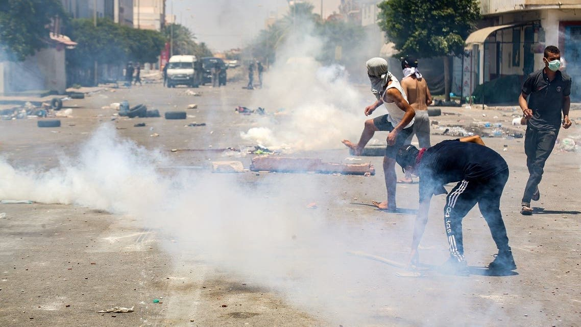 Protesters from Tunisia's Tataouine region throw stones as they clash with security forces, firing tear gas, amidst a demonstration in the southern city on June 21, 2020. (AFP)