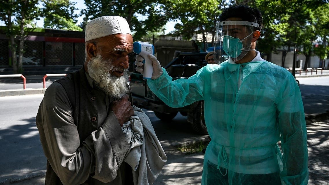 A health worker (R) checks the body temperature of a Muslim devotee as a preventive measure against the COVID-19 coronavirus at the start of the Eid al-Fitr festival which marks the end of the Muslim holy month of Ramadan at Wazir Akbar Khan mosque in Kabul on May 24, 2020. (AFP)