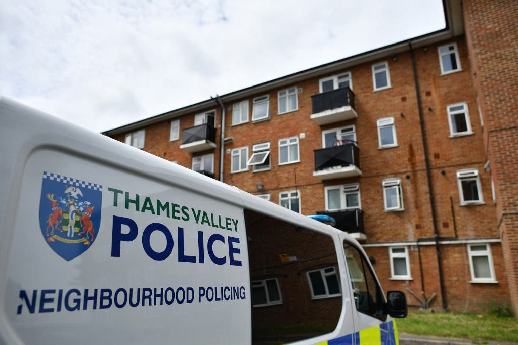 A police van is pictured outside a block of flats where the suspect of a multiple stabbing incident the previous day is believed to have lived, in Reading, west of London, on June 21, 2020. (AFP)