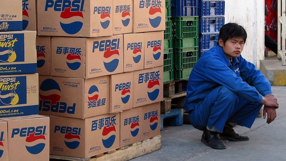 A PepsiCo worker watches over a delivery of the soft drinks to a supermarket in Beijing, 26 May 2003. (AFP)