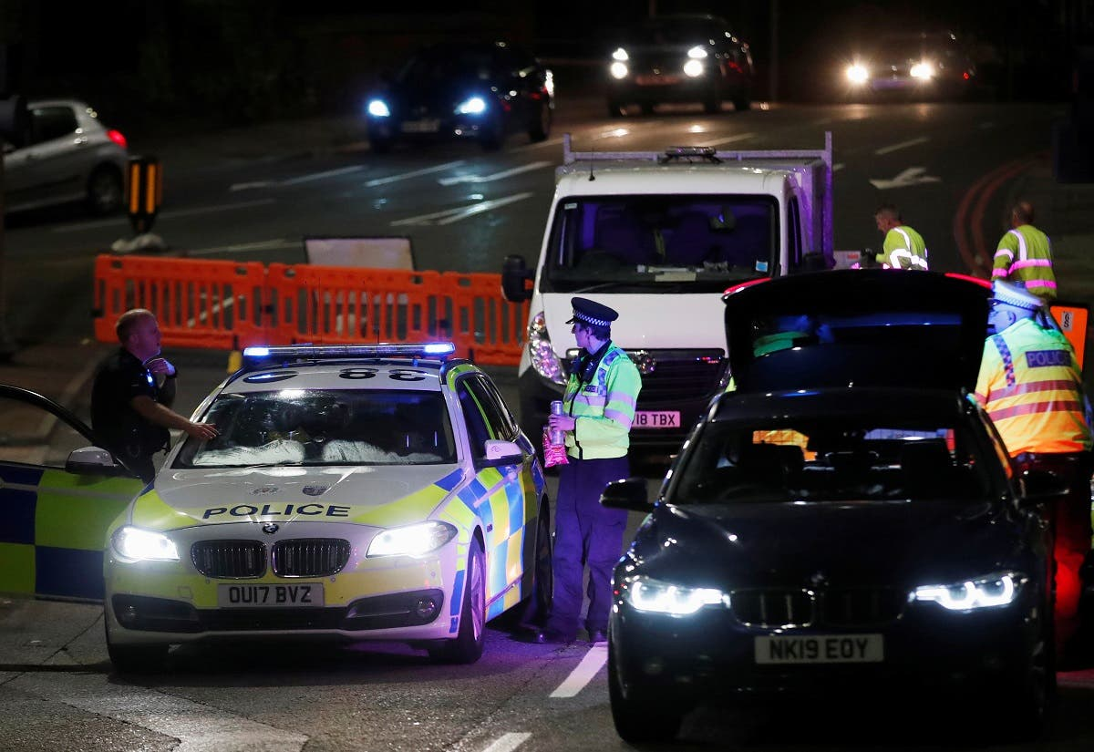 Police officers and their vehicles are seen at a cordon at the scene of reported multiple stabbings in Reading, Britain. (Reuters)