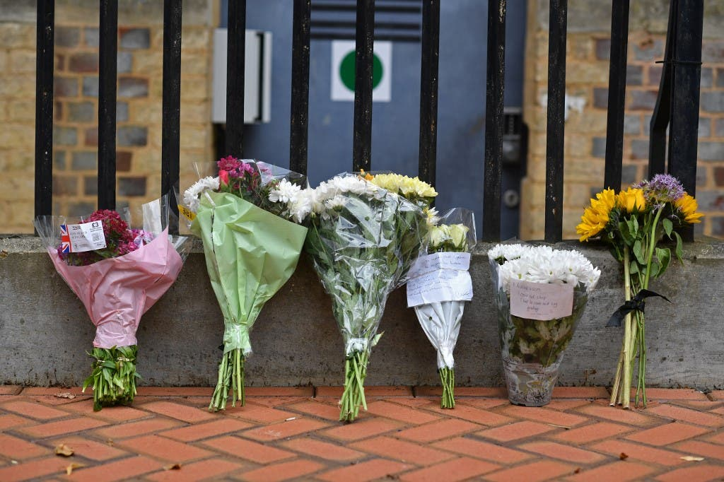 Floral tributes are seen at a police cordon at the Abbey Gateway near Forbury Gardens park in Reading, west of London, on June 21, 2020. (AFP)