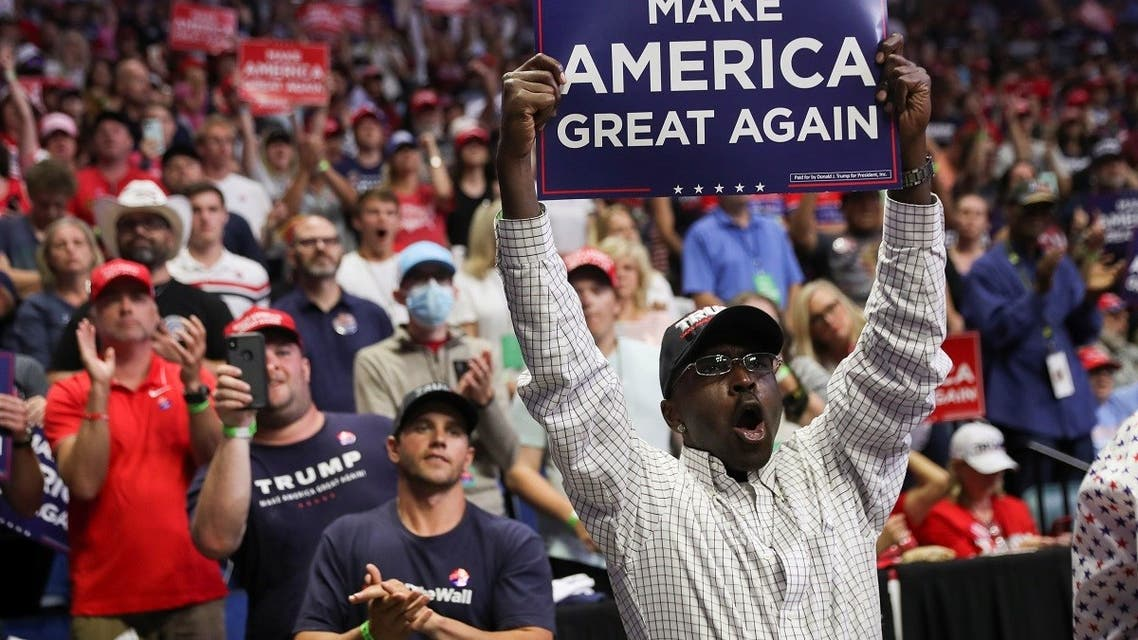 A Black supporter of U.S. President Donald Trump holds up a Make America Great Again sign as the president arrives at his first re-election campaign rally in several months in the midst of the coronavirus disease (COVID-19) outbreak, at the BOK Center in Tulsa, Oklahoma, U.S., June 20, 2020. REUTERS/Leah Millis
