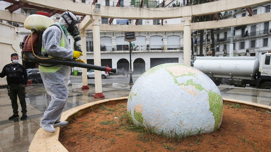 A worker wearing a protective suit disinfects a globe-shaped public garden, following the outbreak of coronavirus, in Algiers, Algeria, March 23, 2020. (Reuters)