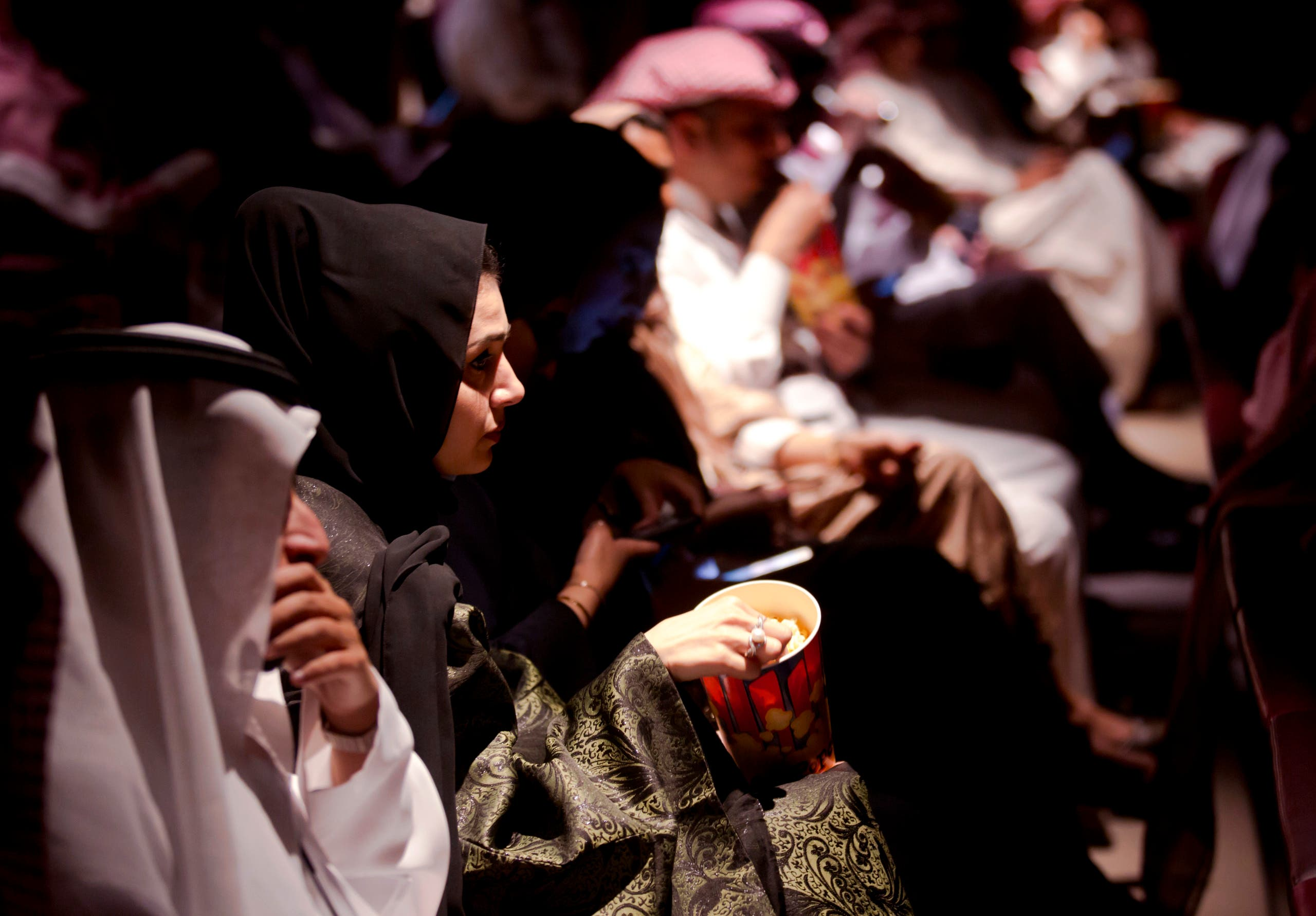 Visitors eat popcorn as they attend an invitation-only screening, at the King Abdullah Financial District Theater, in Riyadh, Saudi Arabia. (File photo: AP)