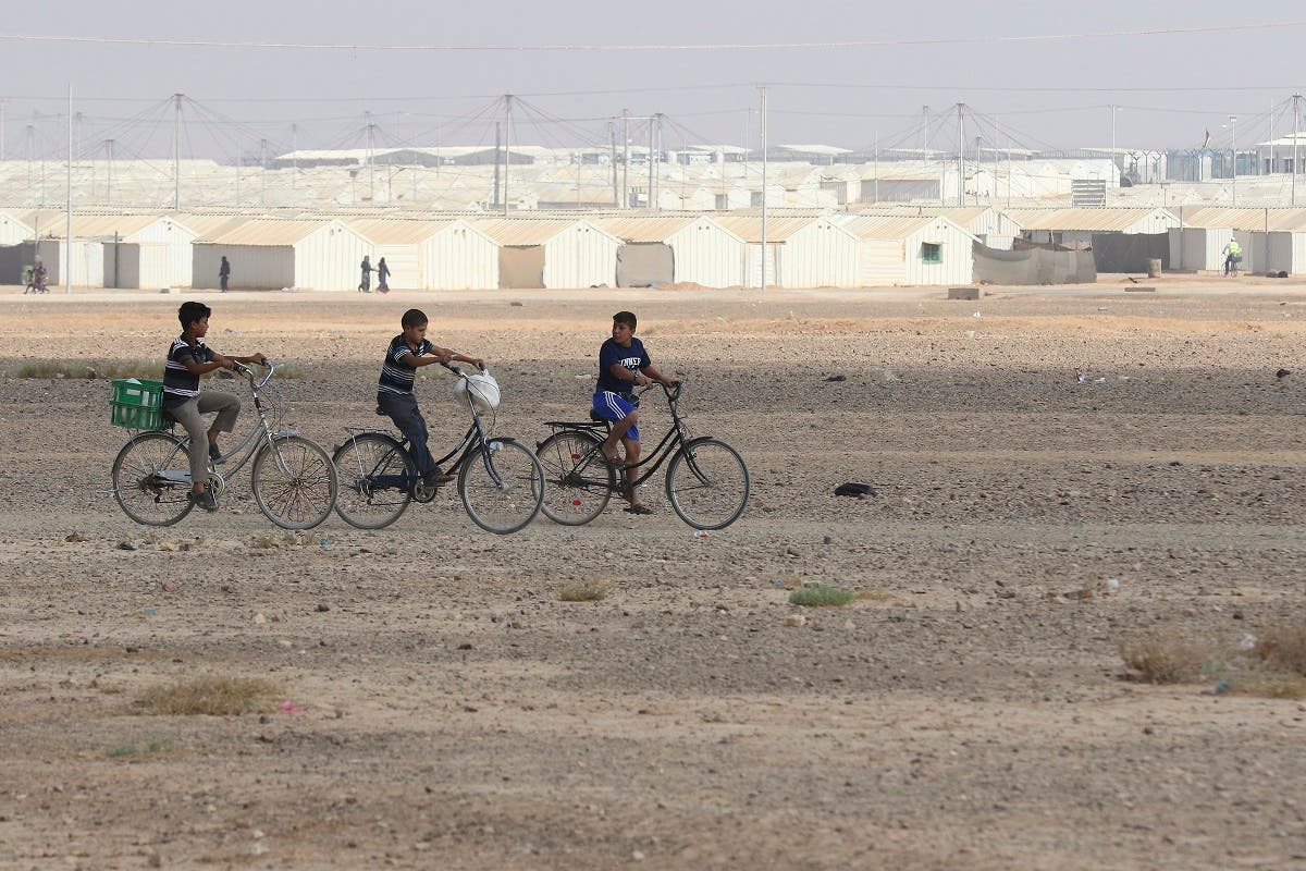 Young Syrian refugees ride their bicycles at the Azraq camp for Syrian refugees in northern Jordan on August 2, 2018. (AFP)