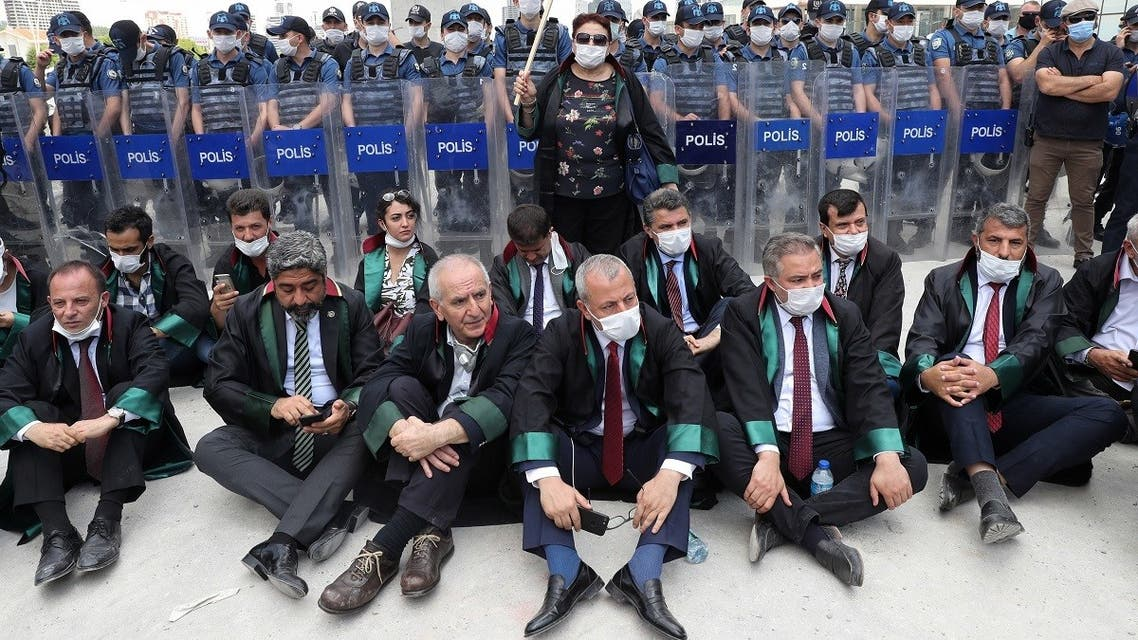 Senior lawyers protesting against a draft bill governing the organisation of bar associations sit on the ground during a rally in front of Turkish riot policemen blocking the road, in Ankara on June 22, 2020. (AFP)