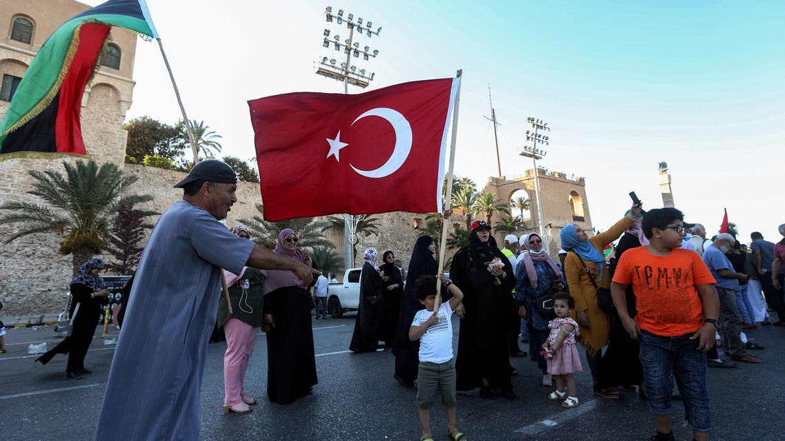 People wave flags of Libya (R) and Turkey (L) during a demonstration in the Martyrs' Square in the centre of the Libyan capital Tripoli, currently held by the UN-recognised Government of National Accord (GNA), on June 21, 2020. The GNA on June 21 denounced Egypt's warning of military intervention in Libya, labelling it a declaration of war, after the Egyptian President warned that if pro-GNA forces advanced on the strategic city of Sirte -- some 450 kilometres (280 miles) east of Tripoli -- it could provoke a direct intervention by Cairo.