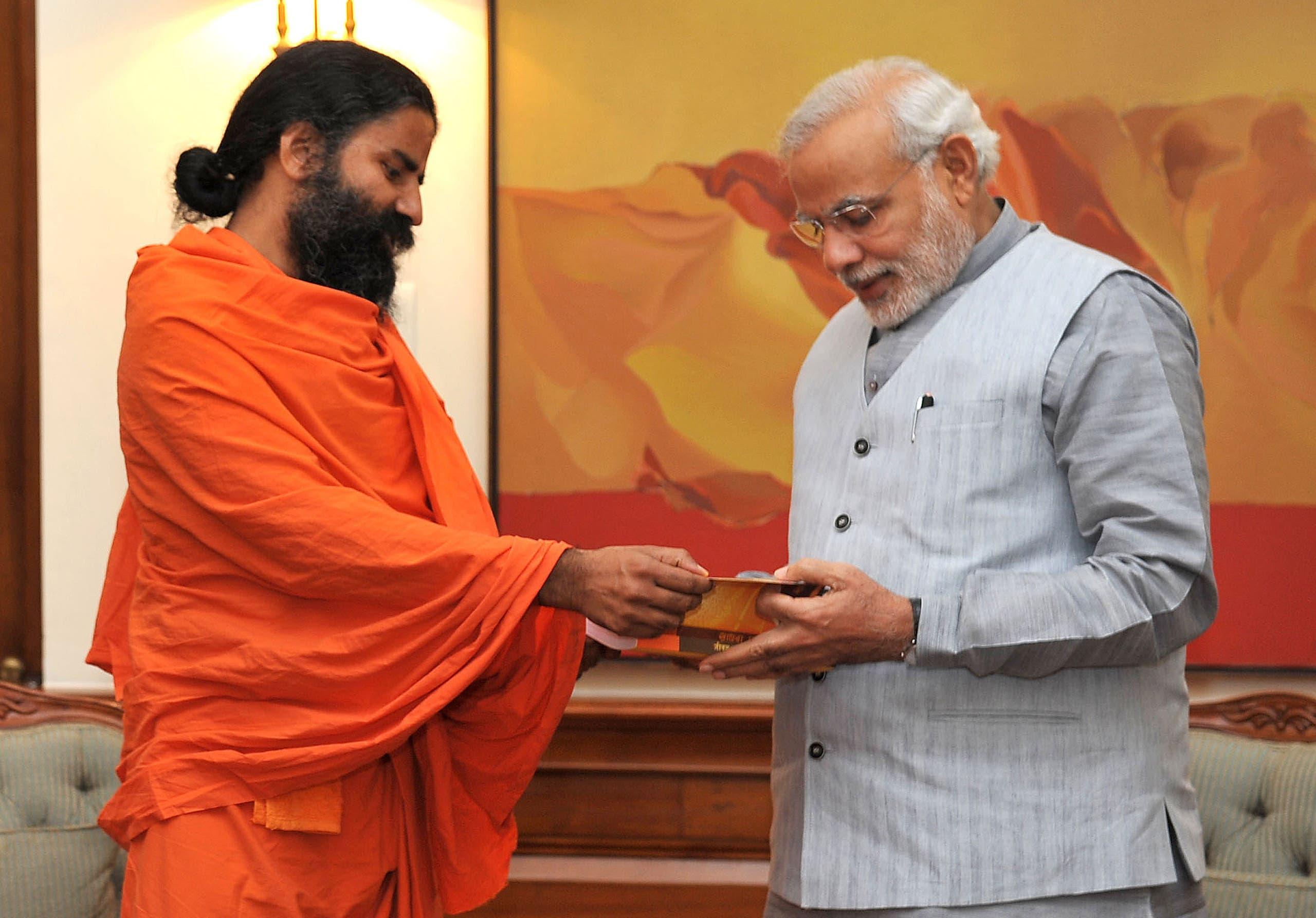 Yoga guru Baba Ramdev (L) calls on Indian Prime Minister Narendra Modi in New Delhi on November 4, 2014. (AFP)