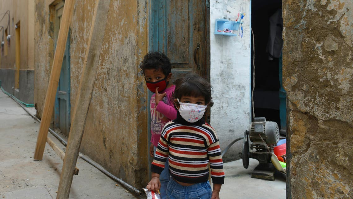 Children wearing facemasks play in front of their house during a government-imposed nationwide lockdown as a preventive measure against the COVID-19 coronavirus in Rawalpindi on March 30, 2020. (AFP)