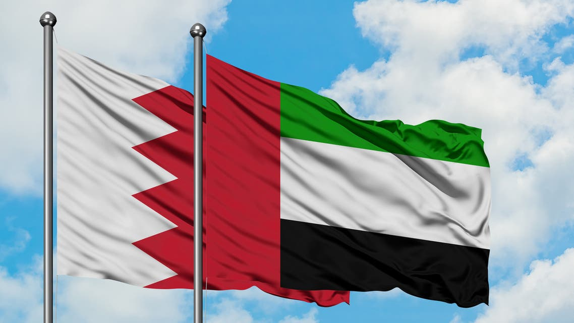 Bahrain and United Arab Emirates flag waving in the wind against white cloudy blue sky together. Diplomacy concept, international relations. stock photo