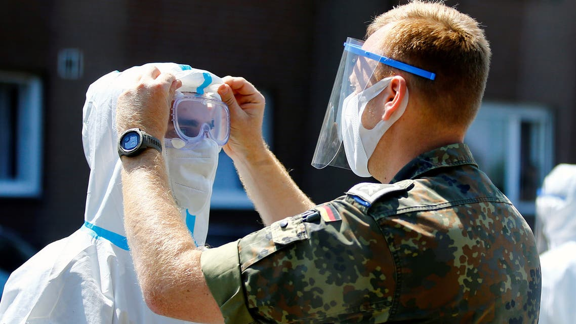 A member of the German Army adjusts the googles of a health professional outside the houses of employees of the Toennies factory, who are under lockdown after a coronavirus disease (COVID-19) outbreak in the meatpacking plant, in Verl, Germany, June 23, 2020. REUTERS/Leon Kuegeler