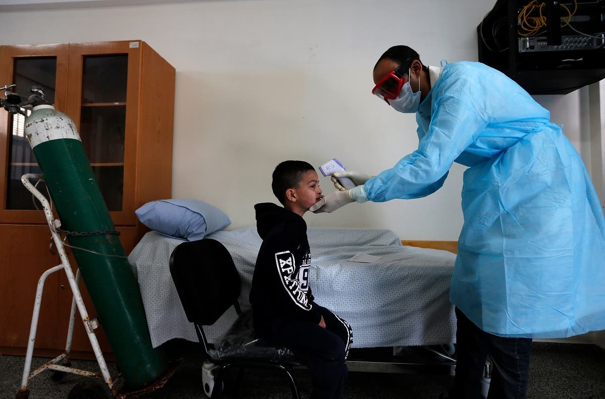 A Palestinian health worker checks the body temperature of a child at a UNRWA school at al-Shati refugee camp in Gaza City on March 18, 2020. (AFP)