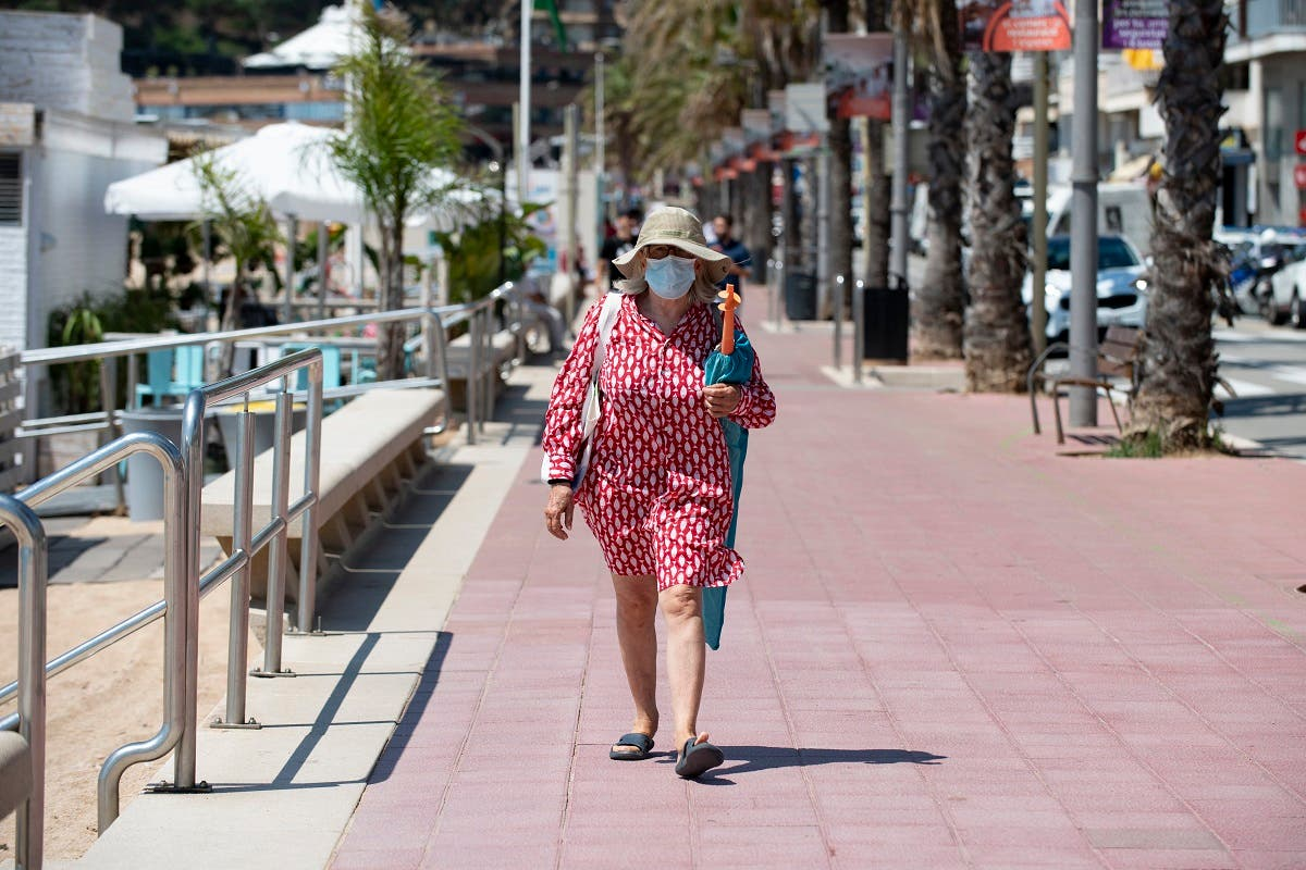 A woman wearing a face mask walks in Lloret de Mar on June 22, 2020 as beaches reopen in Spain. (AFP)