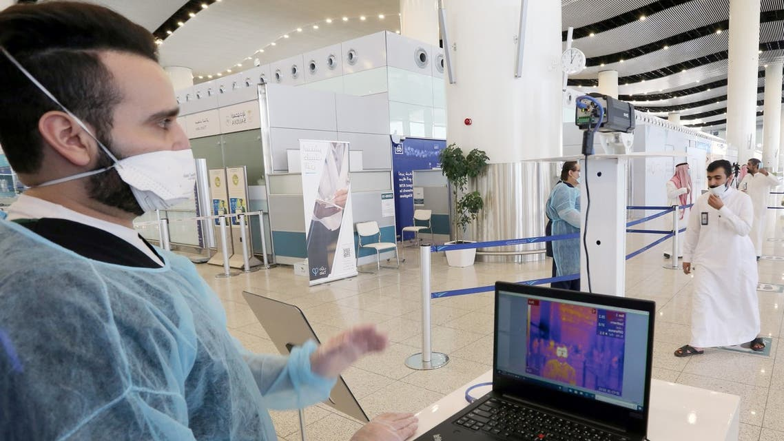 A security man looks at a screen showing the body temperature of travellers, at Riyadh International Airport on May 31, 2020. (Reuters)