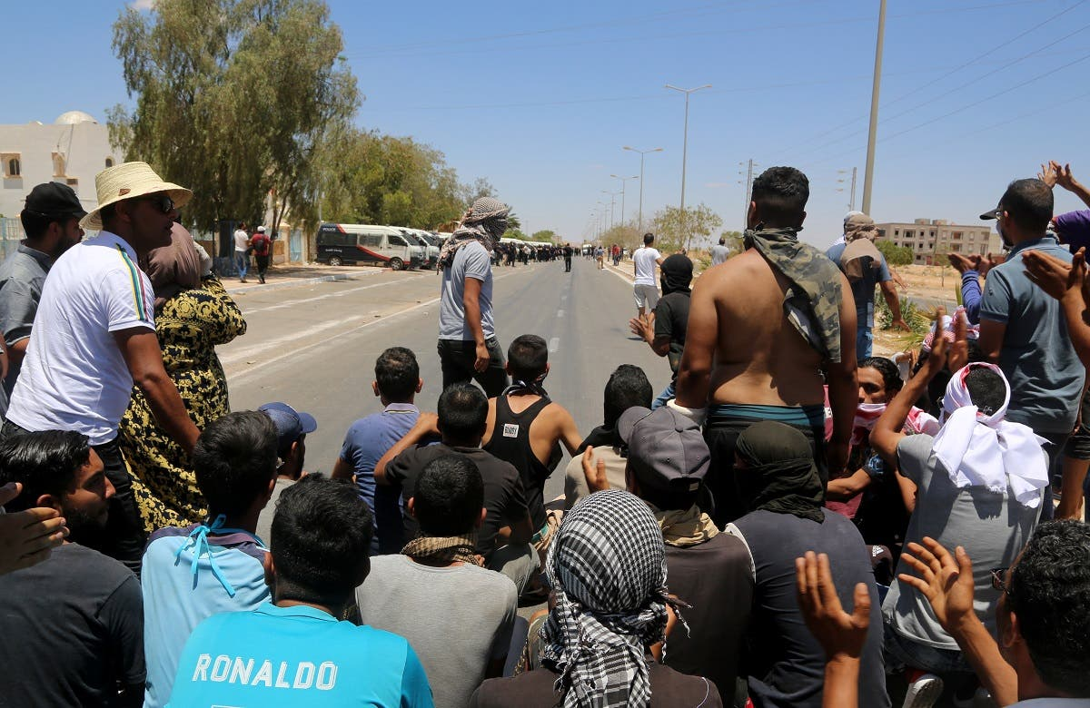 Tunisian protesters block a road leading to the center of Tataouine on June 23, 2020, during a gathering to demand the release of detained protesters who were tried for disrupting public order. (AFP)