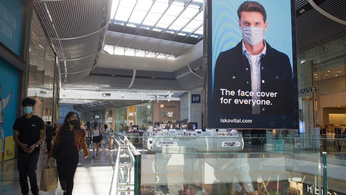 Shoppers wearing protective face masks walk past an advertising screen promoting face coverings in Westfield shopping centre in Stratford, east London on June 22, 2020. Britain's current social distancing guidelines set the distance between each person at two metres to avoid the risk of contamination to coronavirus. There is pressure on the government to reduce this distance in order to give a boost to bars, restaurants and hotels, which are scheduled to reopen next month.