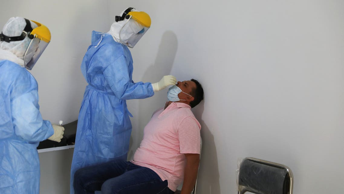 A member of a medical team wearing a protective suit takes a swab to test for the coronavirus disease (COVID-19) at a medical clinic in Tripoli, Libya June 10, 2020. REUTERS/Ismail Zitouny