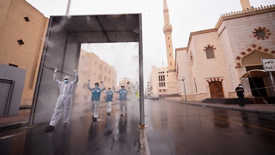 Health volunteers pass through a sterilisation chamber installed to disinfect residents entering and leaving the Naif area in the Gulf emirate of Dubai during the COVID-19 coronavirus outbreak, on April 15, 2020. (AFP)