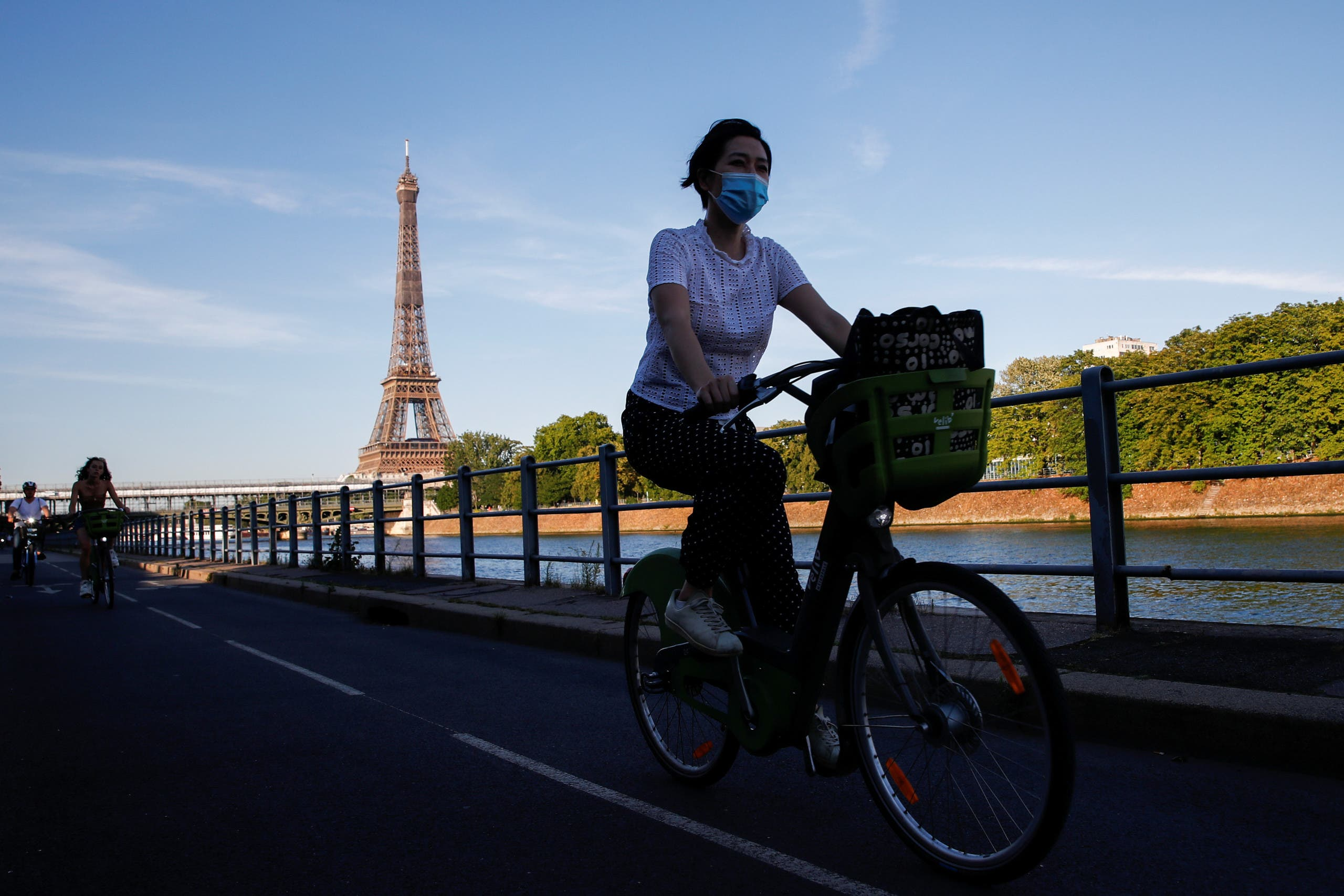 A woman wearing a protective mask rides a bicycle near the Eiffel Tower during a warm and sunny day in Paris as a heatwave hits France, June 24, 2020. (Reuters)