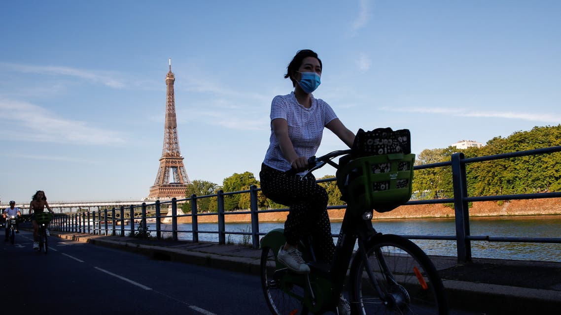 A woman wearing a protective mask rides a Velib bicycle-sharing service near the Eiffel Tower during a warm and sunny day in Paris as a heatwave hits France, June 24, 2020. (Reuters)