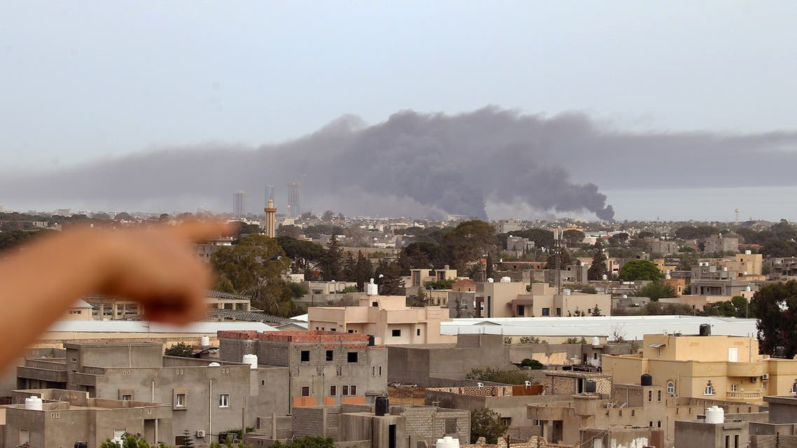 A finger points at smoke rising above buildings in the Libyan capital Tripoli, during reported shelling on May 9, 2020. (AFP)