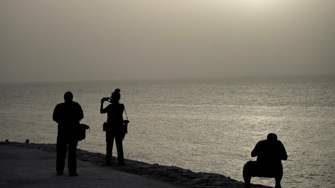 Photographers shoot pictures at the colonial-era fortress El Morro Cabana as dust carried by winds from the Sahara desert shrouds Havana, Cuba, June 24, 2020. (Reuters)