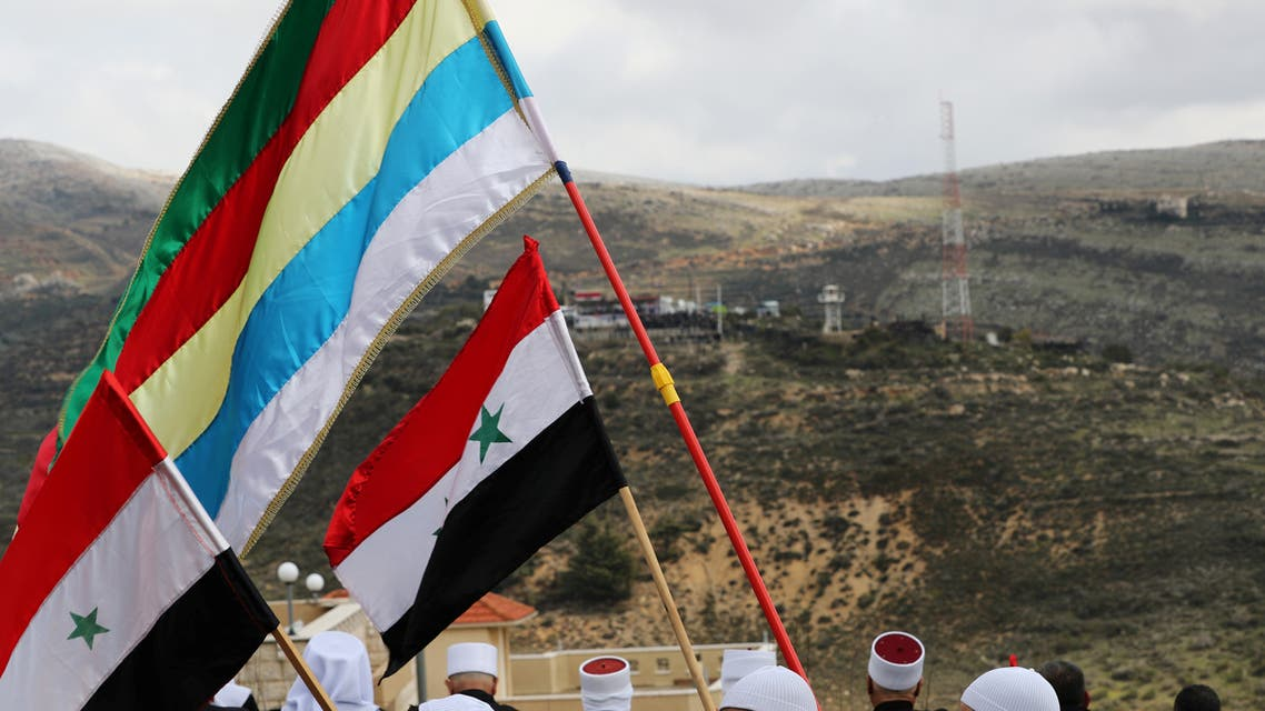 Members of the Druze community holds Syrian and Druze flags as they sit facing Syria, during a rally marking the anniversary of Israel's annexation of the Golan Heights in the Druze village of Majdal Shams, in the Israeli-occupied Golan Heights February 14, 2019. (Reuters)