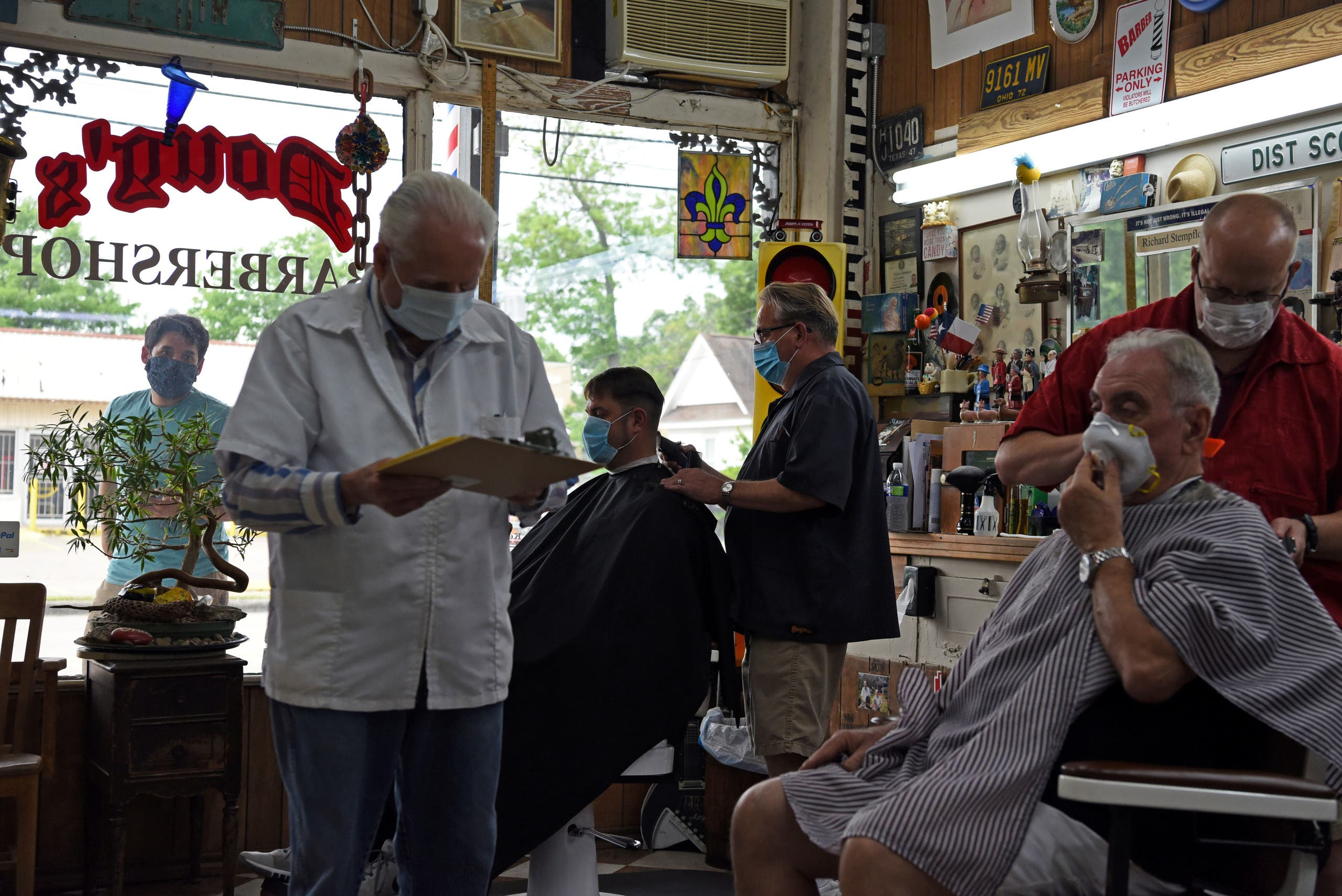 Men receive haircuts as social distancing guidelines are relaxed at Doug's Barber Shop in Houston on May 8, 2020. (Reuters)