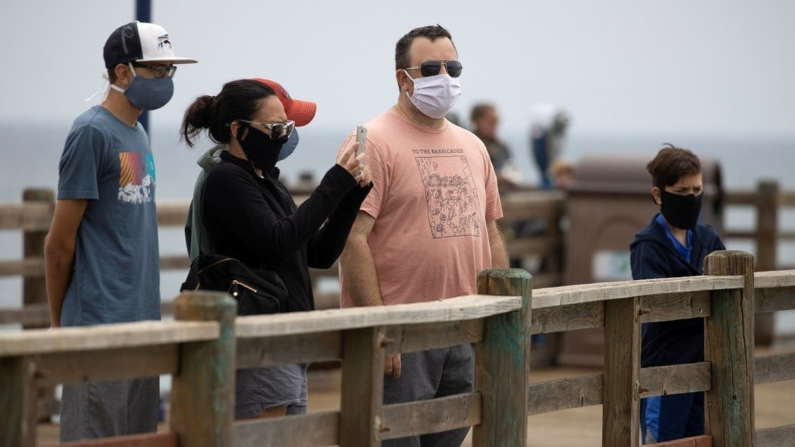 People wear masks as they walk on the ocean pier during the global outbreak of the coronavirus disease (COVID-19) in Oceanside, California, U.S., June 22, 2020. (Reuters)