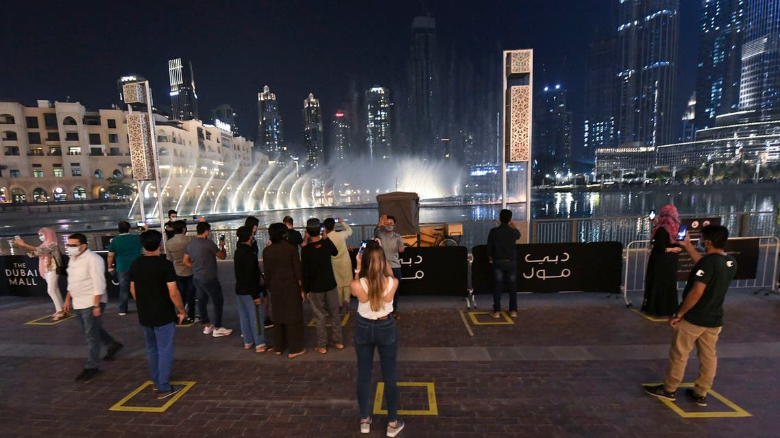 people observe social distancing while gathering to watch the Dubai fountain show which resumes as the Gulf emirate emerges from a lockdown imposed due to the COVID-19 pandemic, UAE, June 2, 2020. (AFP)